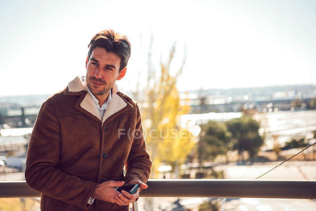 Fashionable man in brown jacket posing outdoors and holding mobile phone — Stock Photo