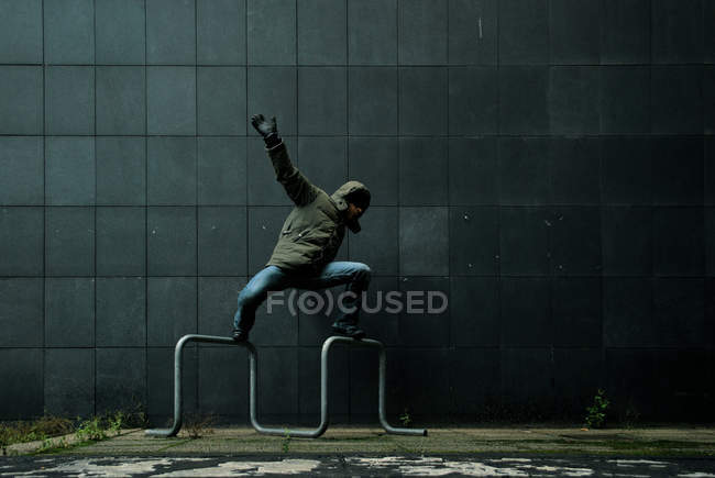 Man standing onto a pipe keeping the balance — Stock Photo