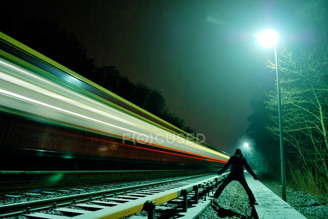Light trail of speeding train at night with man beside — Stock Photo