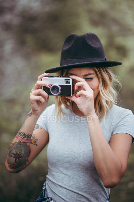 Молода жінка беручи малюнок з ретро камери в природі — стокове фото