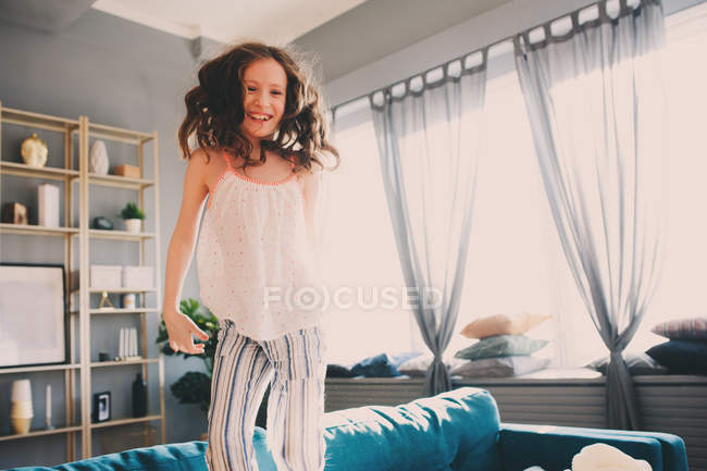 Three quarter length of a smiling young girl at home — Stock Photo