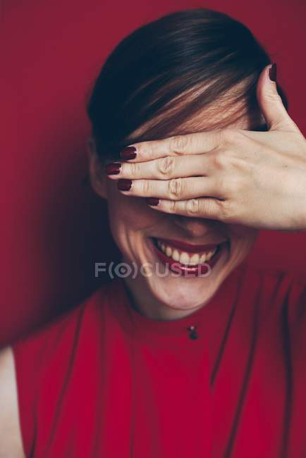 Portrait of smiley woman against red background covering her eyes. — Stock Photo