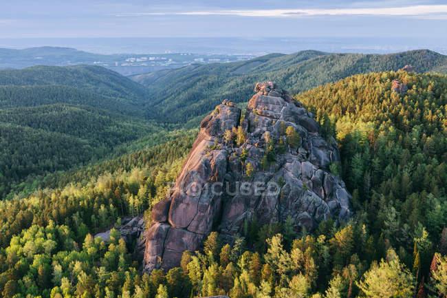 Gran roca rodeada de árboles en las montañas - foto de stock