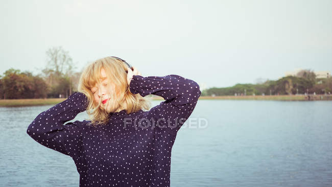 Young teenager with blonde hair listening to music by the lake — Stock Photo