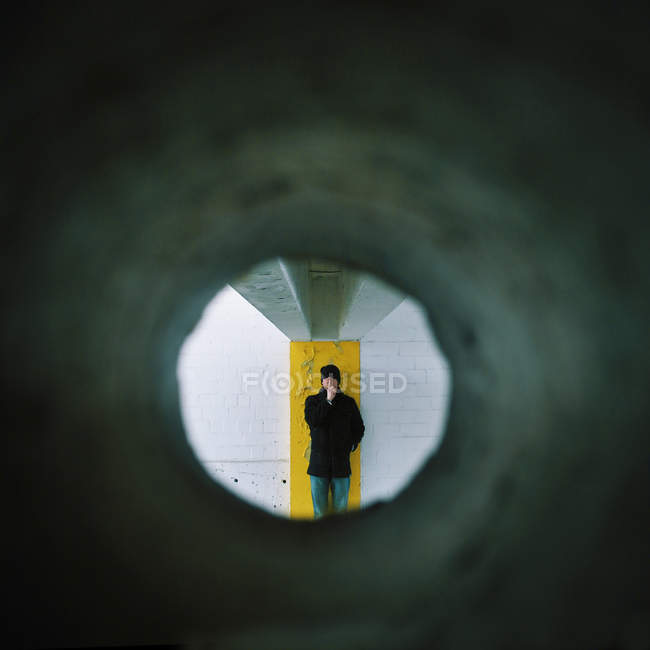 Tunnel vision of a man standing against a wall gesturing to be quiet — Stock Photo
