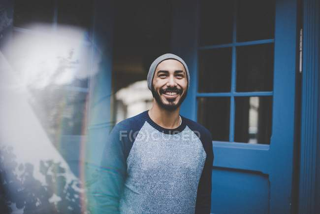Man in hat and casual clothing at blue door — Stock Photo