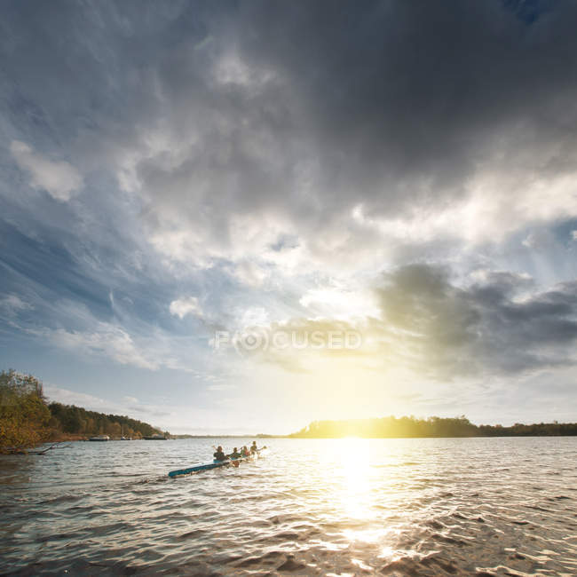 Vue panoramique du peuple dans un canot de bateau dehors en mer pendant le coucher du soleil — Photo de stock