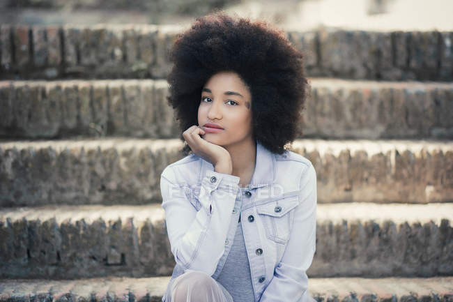 Portrait of young woman with afro hair and denim jacket — Stock Photo