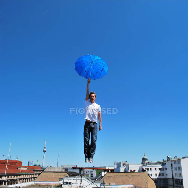 Action shot of a man in mid air holding an umbrella under blue skies in Berlin — Stock Photo