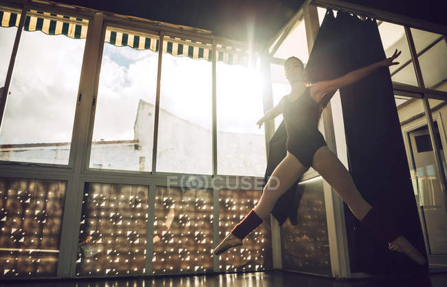 Full length of young woman jumping in ballet studio — Stock Photo
