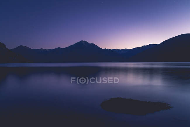 Живописный вид на заснеженные горы, свое отражение в озере на закат, пурпурный закат — стоковое фото