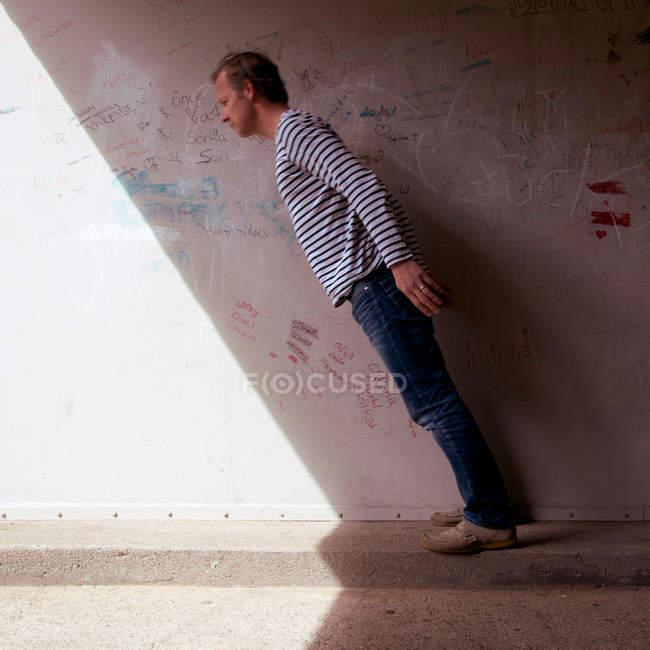 Vista lateral do homem angulado de pé contra a parede. — Fotografia de Stock