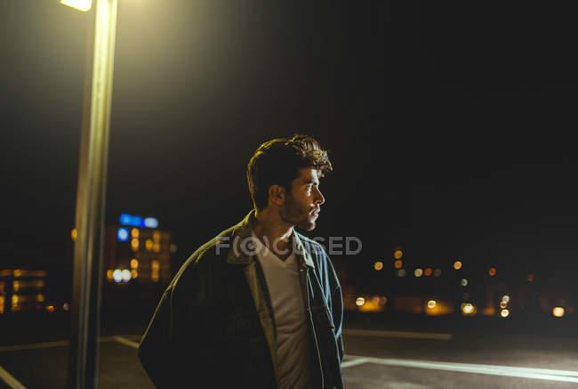 Человек в городе ночью, освещенный огнями — стоковое фото