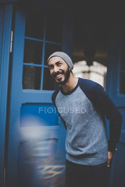 Portrait of laughing young man in hat and casual clothing at blue door — Stock Photo