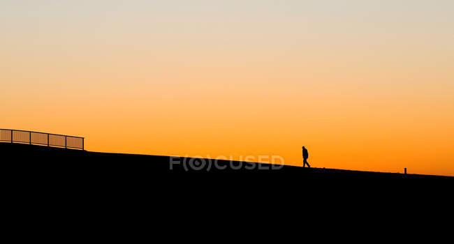 Homme silhouette debout avec ciel orange — Photo de stock