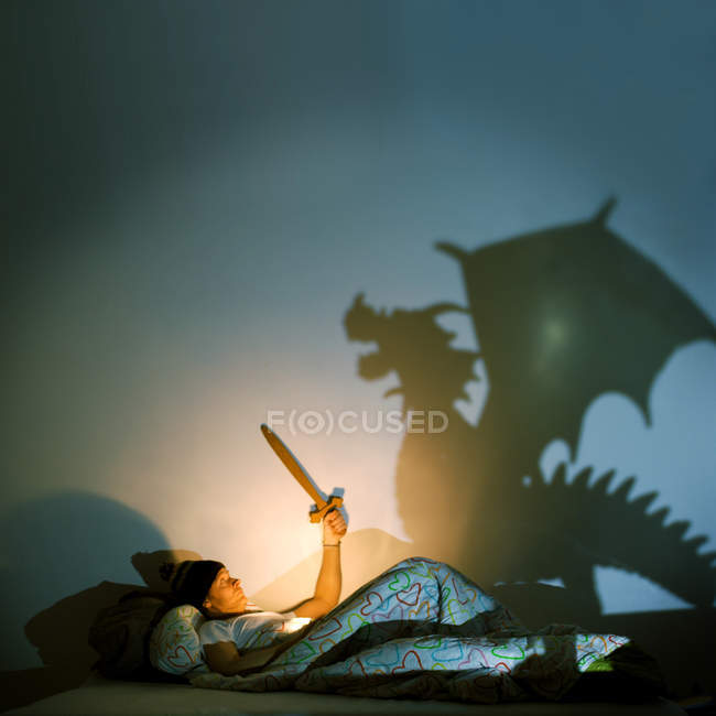 A man holding a sword in bed from a representation of a dragon — Stock Photo