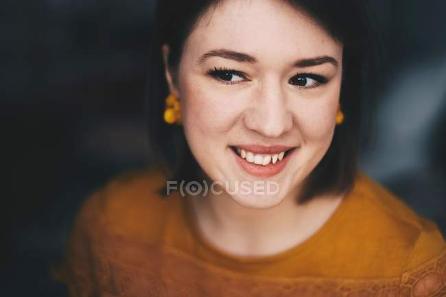 Smiling and attractive young woman with yellow earrings — Stock Photo