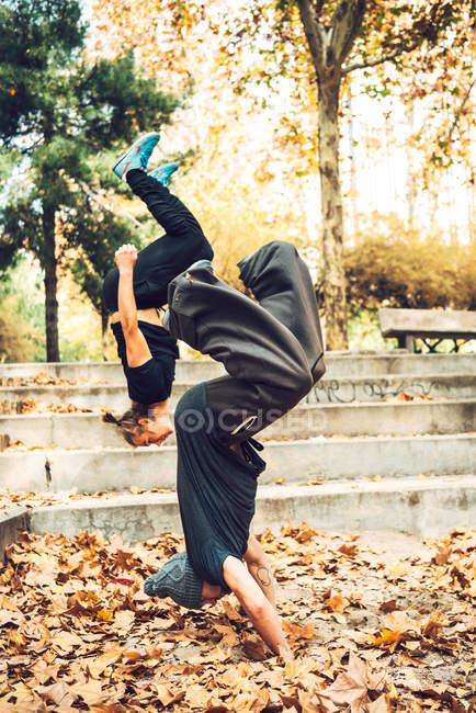 Jeunes hommes exécutant des astuces de parkour dans le parc — Photo de stock