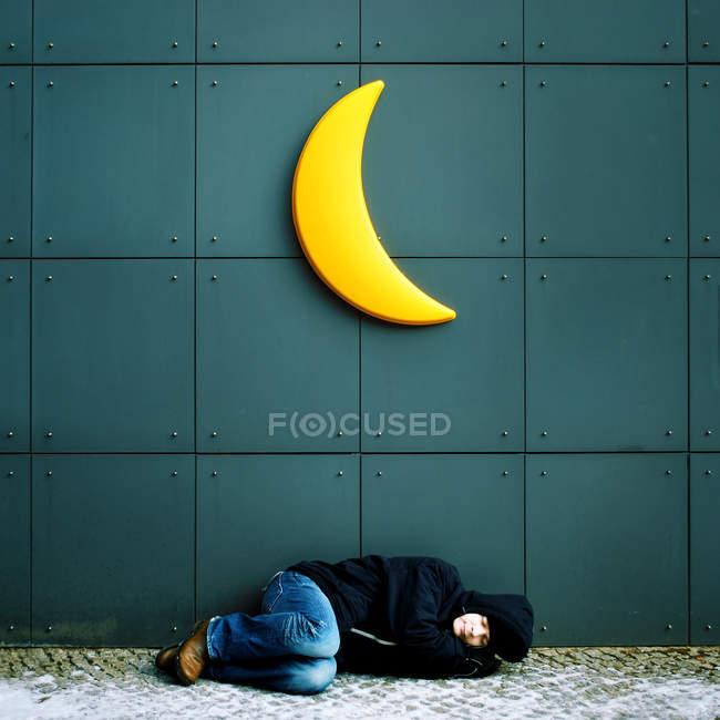 Man sleeping on a floor under moon sign — Stock Photo