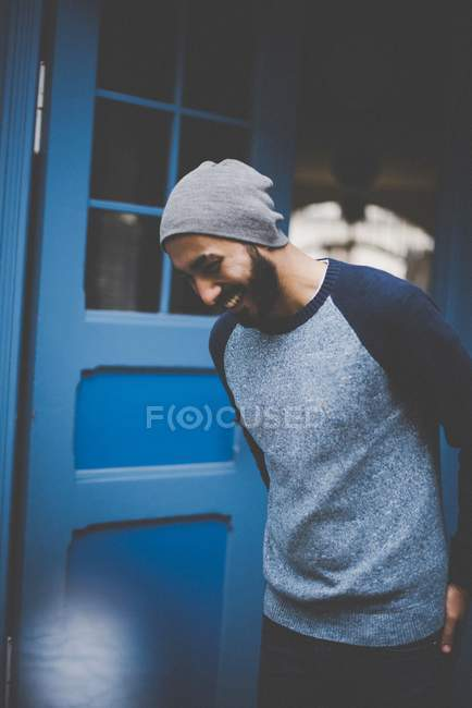 Laughing young man in hat and casual clothing at blue door — Stock Photo