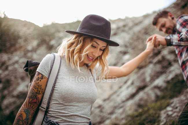 Young couple enjoying nature together and travel hiking in rocky mountains — Stock Photo
