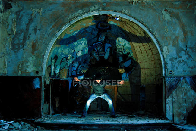 A man standing in an arch full of graffiti in an old abandoned building — Stock Photo