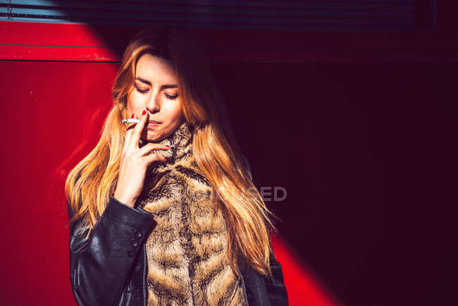 Beautiful young woman with blonde hair smoking against red wall — Stock Photo