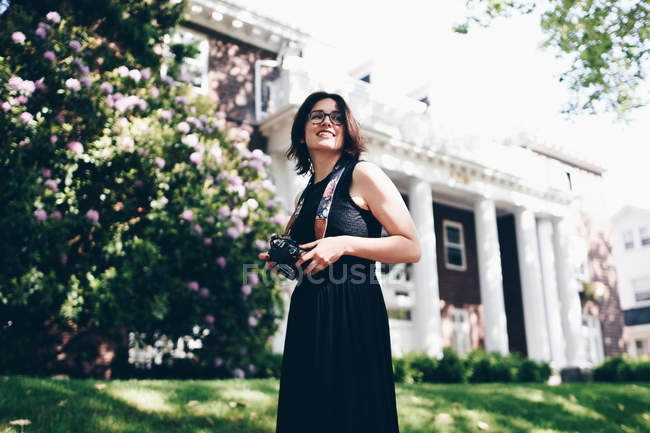 Brunette woman with camera standing at house in black dress — Stock Photo