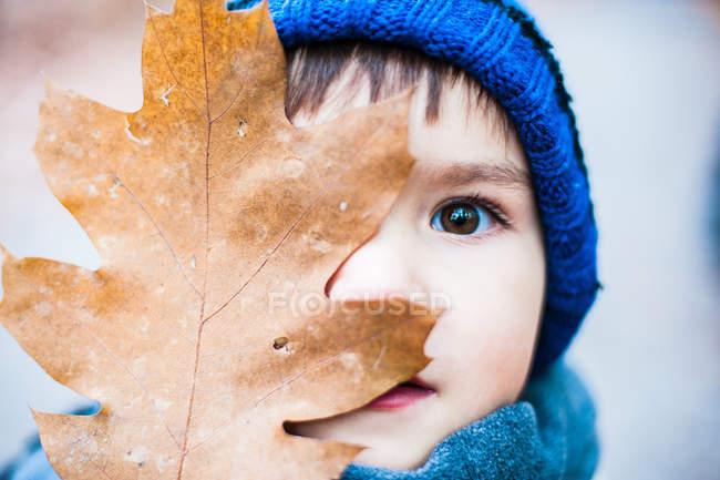 Un jeune garçon couvrant son visage avec une feuille — Photo de stock