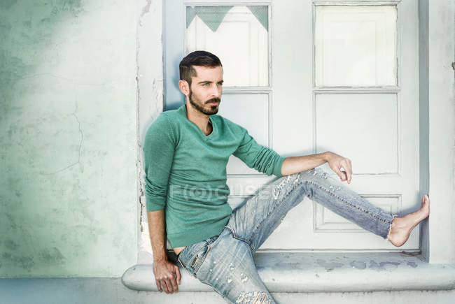A young man in casual clothing sitting against a wall — Stock Photo