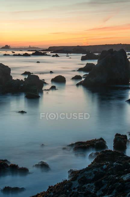Rochers en mer pendant l'exposition de coucher de soleil, longue — Photo de stock