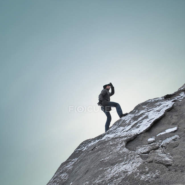 Side view of a man climbing a rocky mountain — Stock Photo