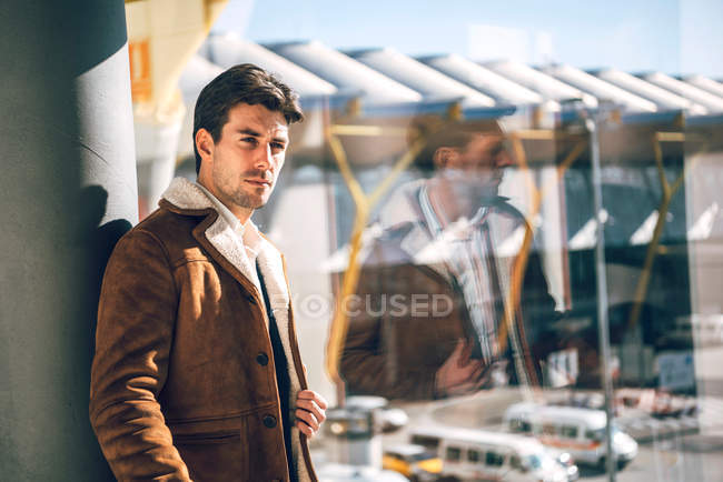 Fashionable man in brown jacket posing in airport — Stock Photo