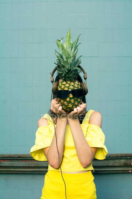 Young woman wearing yellow holding a dressed up pineapple — Stock Photo