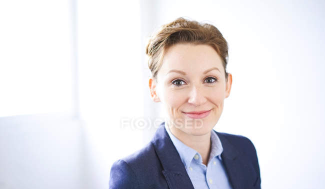 Portrait of smiling business woman in blue jacket, copy space — Stock Photo