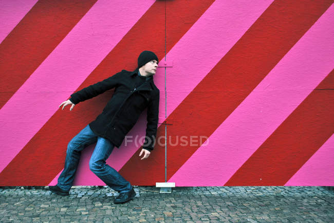 Full length of a crouching down in front of a striped multicolored wall — Stock Photo