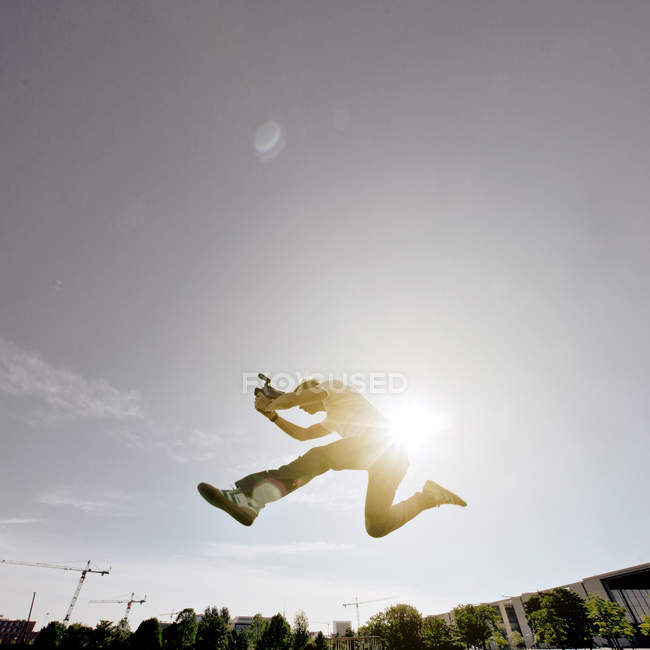 Low angle view of a man jumping in mid air under a clear sky — Stock Photo