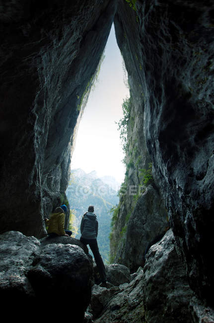 Adventurous couple standing on the rocks overlooking the mountains — Stock Photo