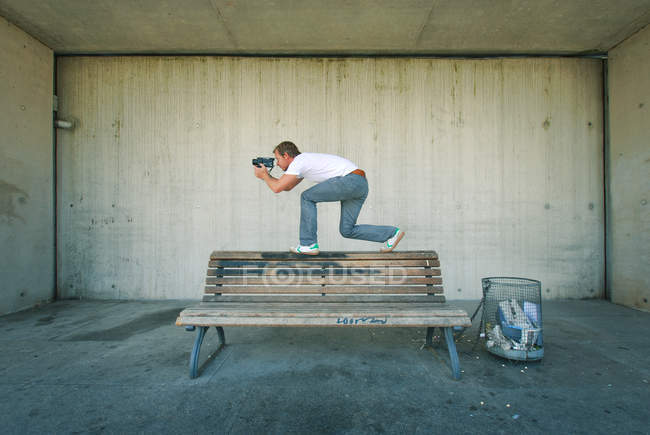 Man crouches on a bench and photographing on camera — Stock Photo