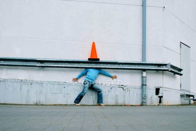 A man hiding underneath a traffic cone against a white wall — Stock Photo