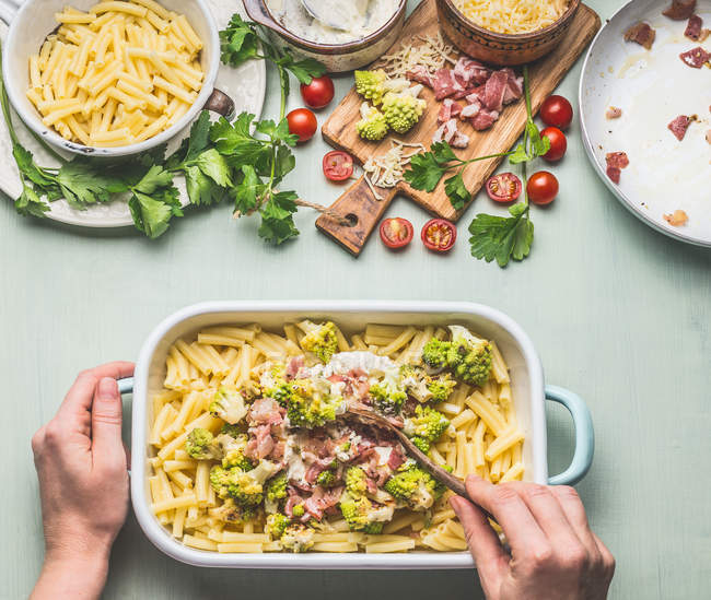 High angle view of human hands preparing food in a dish — Stock Photo