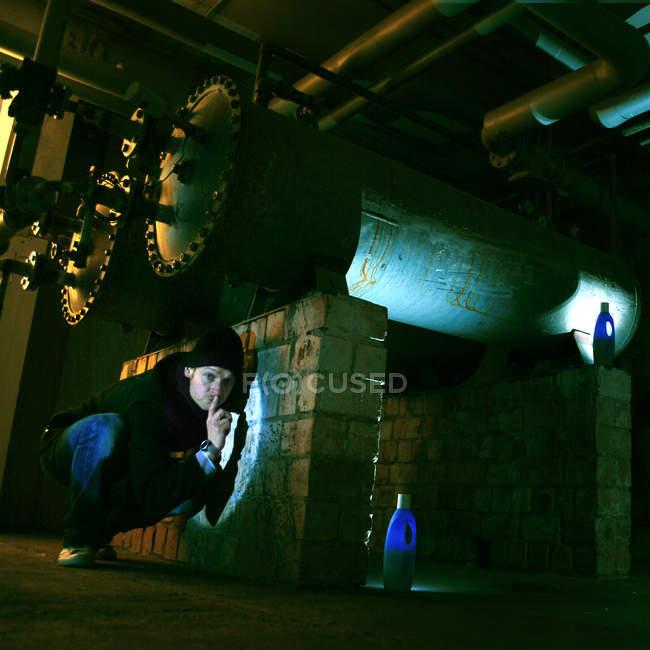Ein Mann kauerte Gestikulieren um ruhig zu sein, in einer Fabrik — Stockfoto