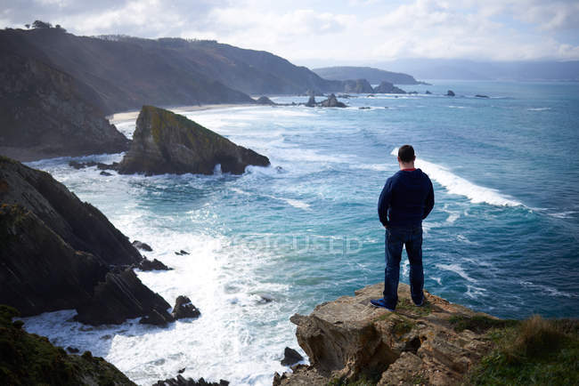 Back view of man standing on rock by sea waves and Gigantic rock formations — Stock Photo