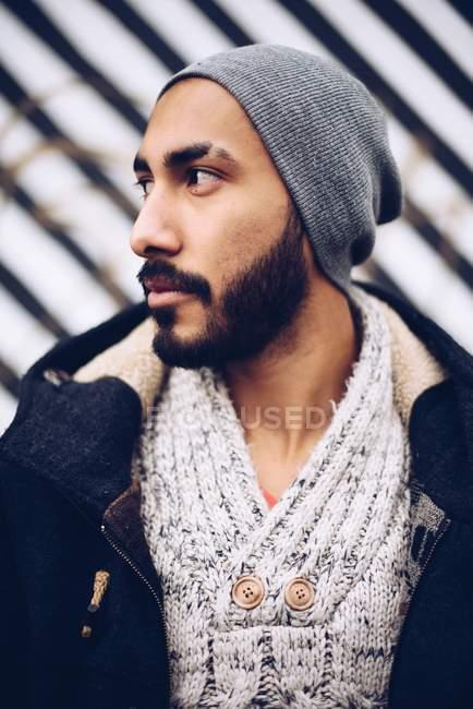 Portrait of handsome Hispanic man in hat and warm sweater with jacket — Stock Photo
