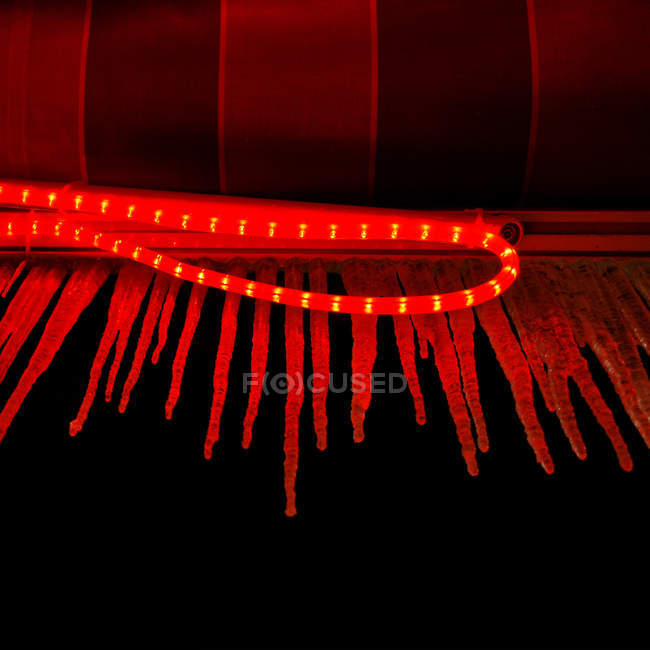 Close up view of an illuminated red light against a dark background — стоковое фото