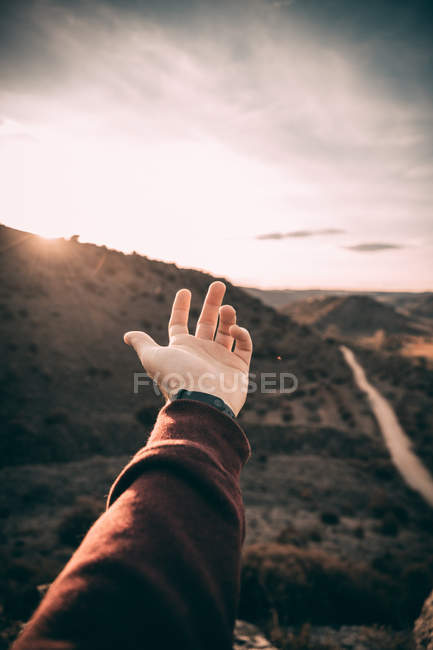 Cropped image of male hand reaching out to landscape — Stock Photo