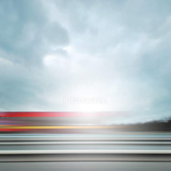 Proposition floue d'un déplacement rapide train sentiers sur une journée nuageuse — Photo de stock