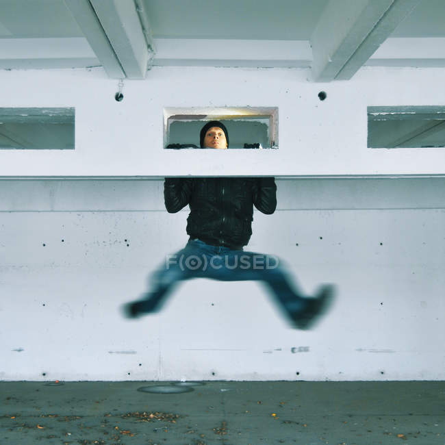 Action shot of a man in mid air hanging off part of a building — Stock Photo
