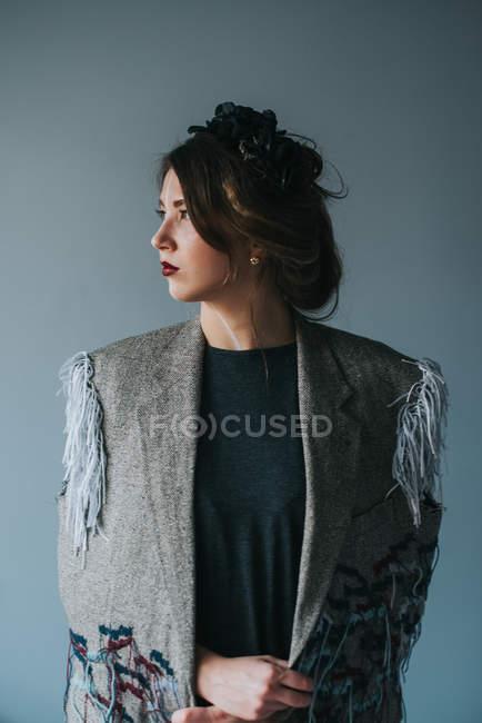 Studioaufnahme der jungen Frau stand vor grauem Hintergrund — Stockfoto