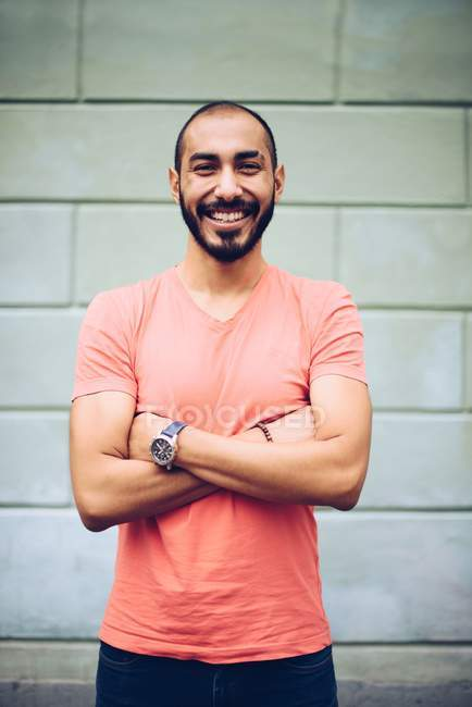 Handsome Hispanic smiling bearded man in casual clothing posing with crossed arms — Stock Photo